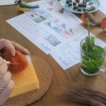Op deze foto zie je iemand een workshop vogeltje naaldvilten volgen. Je ziet 2 handen die met een viltnaald een roodborstje maken van wol, door te prikken met de naald blijft de wol aan elkaar vast zitten vorm je een vogeltje. Ook zie je de geschetste handleiding op tafel liggen, naast de verse munt thee en huisgemaakte chocolade. AtelierSpulli staat voor Ontspanning door Creativiteit. Samen met vriendinnen in een ontspannen sfeer de techniek van het Naaldvilten leren.