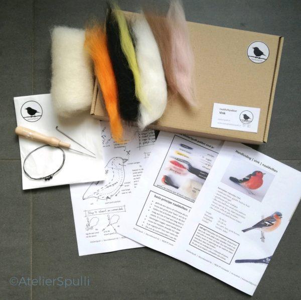 Op deze foto zie je de inhoud van een Vink Naaldvilt Knutselpakket. Met de gekleurde wol, de viltnaalden, de oogjes en staaldraad voor de pootjes kun je deze vogel naaldvilten. Je ontvangt ook een handleiding en kan de instructiefilmpjes bekijken op Youtube. Creatief, knutselen thuis of kom een workshop volgen bij AtelierSpulli.